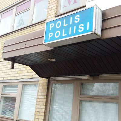 En blå skylt med texten Polis Poliisi ovanför en dörr på ett hus med gula tegel.