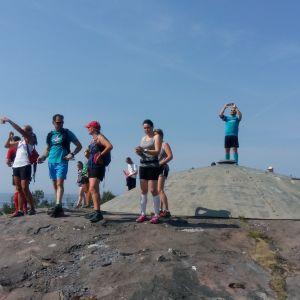 En grupp löpare står uppe på och runt ett stridsvärn på Örö. De deltar i stiglöpning på ön, men har stannat för att ta foton.
