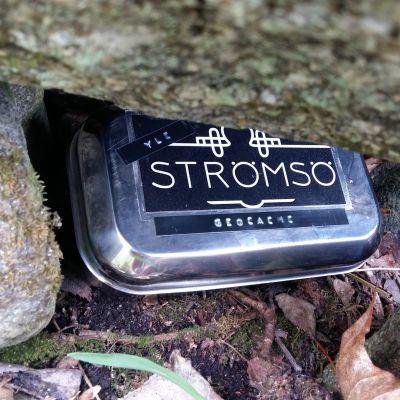 En plåtlåda undangömd under några gråstenar ute i naturen.