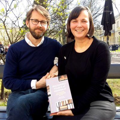 Stefan Nygård och Henrika Tandefelt visar fram jubileumshistoriken över Finlands svenska författareförening 1919-2019.