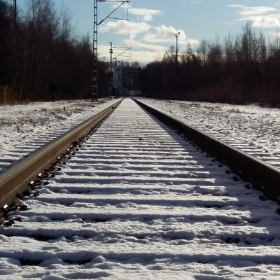 Ett tomt järnvägsspår en solig vinterdag med snö.