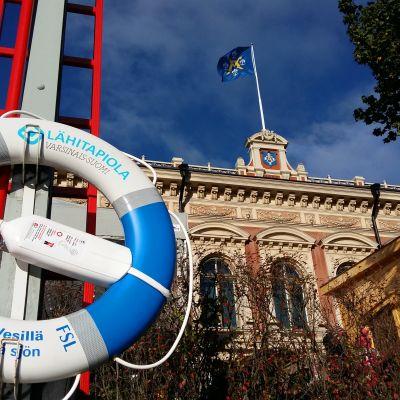 En blåvit livboj hänger vid ån rätt utanför Åbo stadshus, där stadens flagga fladdrar i vinden.