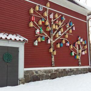En röd husvägg där man har spikat upp femtio fågelholkar och björkstammar som formar två träd.