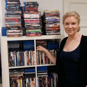 Filmproducenten Leila Lyytikäinen poserar vid en dvd-hylla