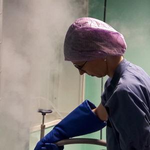 Laborant fyller hinkar med flytande kväve, ser ut som skum eller vit ånga, i ett laboratorium.