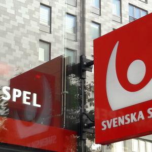 En husfasad med skylt som sticker ut med Svenska Spels logga.