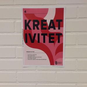 """Röd plansch med texten: """"Kreativitet"""" upphängd på en vit tegelvägg."""