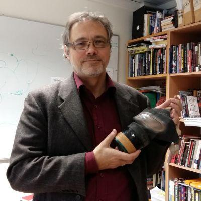 Professor Mats FRidlund, med gasmask  handen, framför sin bokhylla