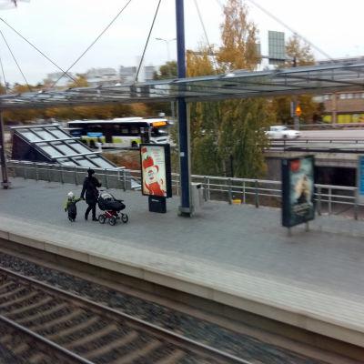 Äiti lasten kanssa Espoon juna-asemalla.