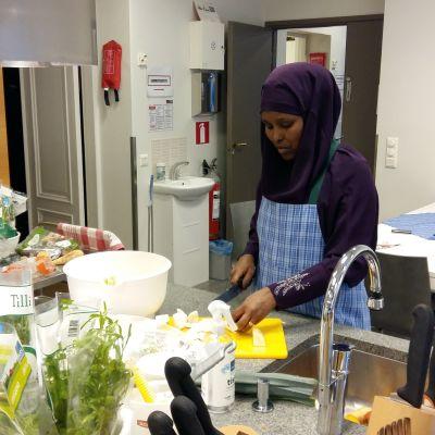 En kvinna i övningsköket lär sig laga finsk mat.