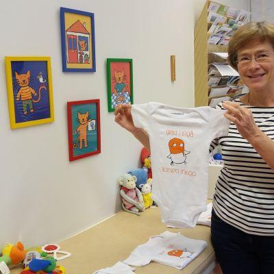 Hälsovårdare Regina Bergström håller upp en babybody med en skrattmås och texten glad i Ingå på.