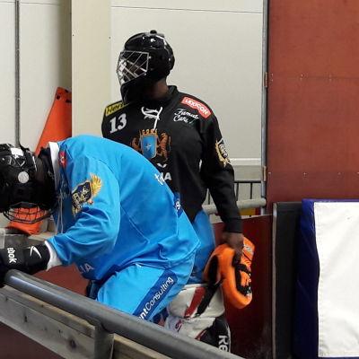 Spelarna klär på skridskoskydd efter träningen.