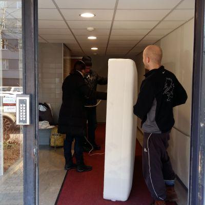 en man bär på en madrass i en dörröppning