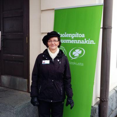Kvinna framför Centerns reklamskylt.
