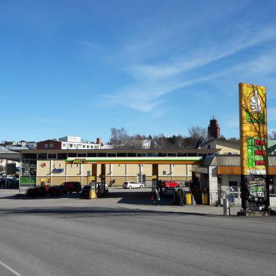 En bensinmack och en butik vid en gata.
