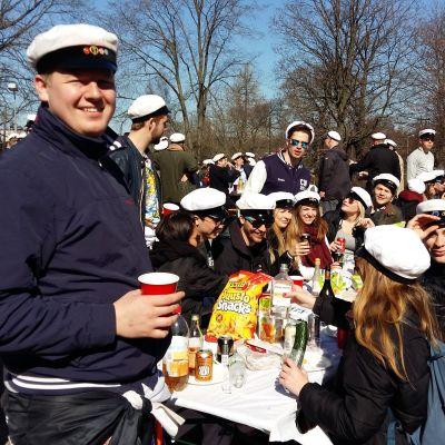 Hankens studentkår SHS har samlats kring ett picknickbord i sina vita studentoveraller.