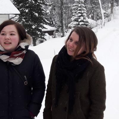 Nora Marie och Katriina på snöklädd backe, utanför trähus i Tromsö.