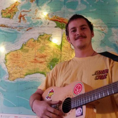 Ung mörkhårig man med mustasch och skägg och gul kortärmad blus. Han står framför en stor karta med en gitarr