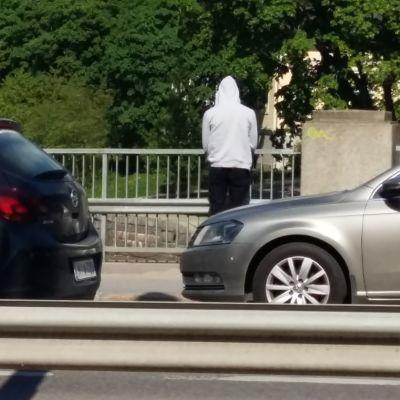 Ung man i ljus munkjacka står på Domkyrkobron och blickar ut över Aura å. Två bilar susar förbi honom