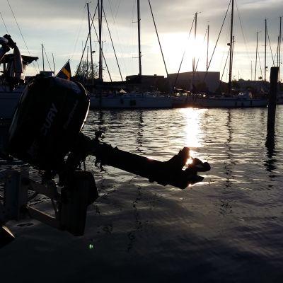 En svart utombordsmotor hänger bak på en segelbåt i en småbåtshamn.