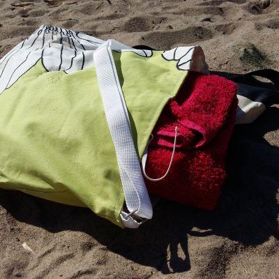 En öppen blommig väska med en röd badhanduk som sticker upp, placerad på en badstrand.