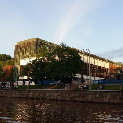 Den nyrenoverade Åbo stadsteater fasad lyses upp av kvällssolen en sommarkväll.