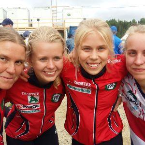 Yvonne Gunell, Ida-Marie Cederberg, Alexandra Enlund och Amy Nymalm i Pargas IF:s röda tävlingsdress kramar om varandra efter Jukolakavlen 2019.
