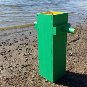 En grön vattenkikare av trä som är placerad i vattenbrynet på en sandstrand.