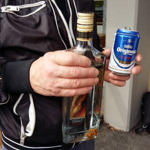 En man håller i en flaska starksprit och en burk öl.