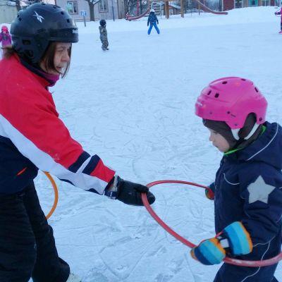 Lastenhoitaja Annukka Stolt opettaa lasta luistelemaan