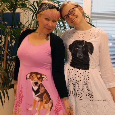 Katukoirien auttajat Riikka Hietala ja kuvataiteilija Sanni Seppä esittelevät Sepän kuvittamia mekkoja.
