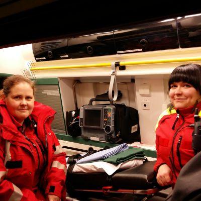 Ensihoitajat Kati Lehtimäki ja Silja Hongisto istuvat ambulanssissa Nauvossa.