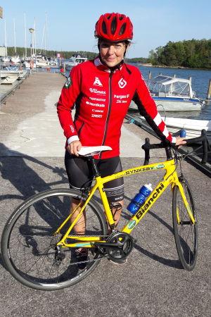 Mariella Ramstedt i full cykelutrustring bredvid sin begagnade Team Rynkeby-cykel