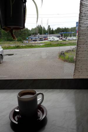 kopp på bord, inne i korg, fönster mot vägen. på andra sidan en bensinmack