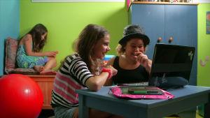 Tyttöjä tietokoneen ja puhelimen ääressä