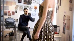 Raf Simons tarkastelee Diorin vintage-mekkoa. Kuva dokumenttielokuvasta Dior ja minä (Dior and I).