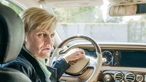 Nainen istuu autossa kuskina ja kurkkaa takapenkille.