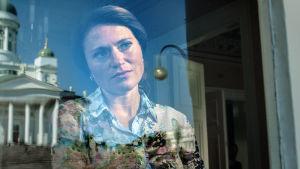 Presidentti-sarjan Petra Pennanen katsoo ulos ikkunan takaa.