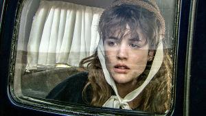 Nuori nainen katsoo ulos auton ikkunasta.