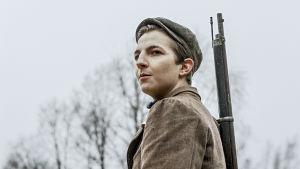 Aktivistit elokuvan yksi päähenkilöistä seisoo ase olallaan ja katsoo kaukaisuuteen.