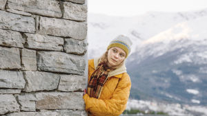 Gunnhild kurkistaa talon takaa ja taustalla jylhät vuoristomaisemat.