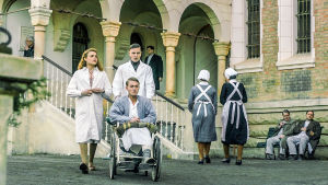 Hoitajat ja pyörätuolipotilas sairaalan pihalla sarjassa Charité (toinen tuotantokausi)