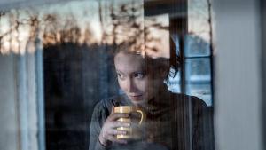 Nainen ikkunan takaa kuvattuna, kahvikuppi kädessä katsoo ulospäin.