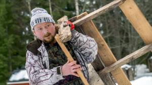 Manu Soininmäki kantaa nikkaroimaansa puukehikkoa.