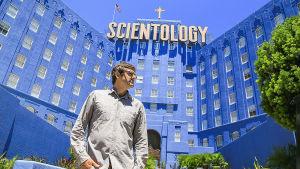 Theroux seisoo scientologien sinisen ja valtavan päämajan edessä.