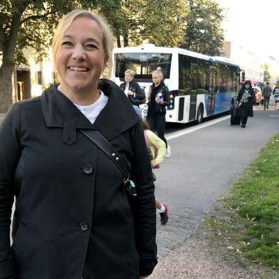 Silja Lindblad står vid busshållplats, i bakgrunden människor och buss.