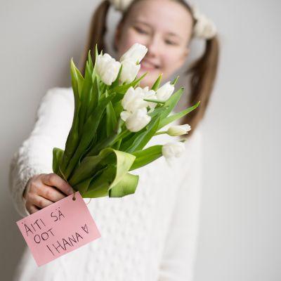 Tyttö ojentaa äitienpäiväkukkia