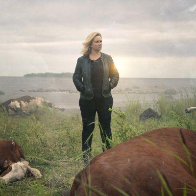 Maria Sidin esittämä KRP:n rikostutkija seisoo nurmella, jolla makaa kuolleita lehmiä.