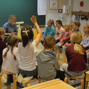 Ettorna sitter i en ring i klassrummet. en flicka markerar.