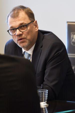 Statsminister Juha Sipilä sitter på ett möte.